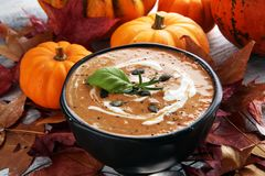 Roasted pumpkin and carrot soup with cream and pumpkin seeds on stock image