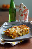 Roasted pumpkin lasagna. On a rectangle gray plate with a bottle of mineral water and serviette Stock Photo