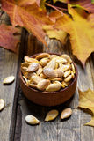 Roasted pumpkin seeds. In bowl and autumn leaves Royalty Free Stock Photo