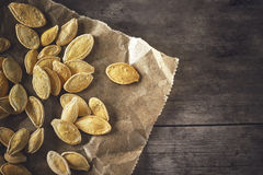 Roasted pumpkin seeds. On grey rustic wooden background. Top view with copy space Stock Images