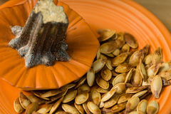 Roasted pumpkin seeds on orange plate. Stock Photography