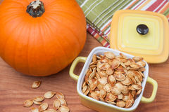 Roasted pumpkin seeds and pumpkin - top view Royalty Free Stock Images
