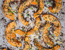 Roasted pumpkin slices with herbs on baking paper. Closeup Stock Images