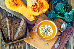 Roasted pumpkin soup with cream, fresh pumpkins and pumpkin seeds in plate on wooden background. Copy space. Close-up Stock Photos