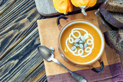 Roasted pumpkin soup with cream, fresh pumpkins and pumpkin seeds in plate on wooden background. Copy space. Close-up Royalty Free Stock Photography