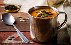 Roasted pumpkin soup in metal mug with seeds and smoked paprika, on rustic wooden background. Royalty Free Stock Photo