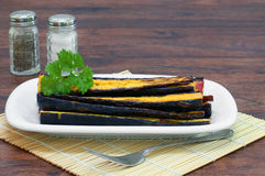 Roasted Purple Carrots stacked on a serving dish. Stock Photo