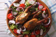 Roasted quail and fresh vegetables close-up. horizontal top view. Roasted quail and fresh vegetables close-up on a plate. horizontal view from above Stock Images