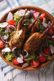 Roasted quail and fresh vegetables close-up. vertical top view. Roasted quail and fresh vegetables close-up on a plate. vertical top view Royalty Free Stock Photography