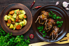 Roasted quail on a spit on a ceramic bowl with greens. Baked potato Royalty Free Stock Photography