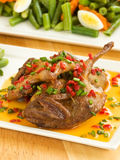 Roasted quails. Dinner plate with roasted quails in saffron sauce and vegetable garnish. Shallow dof Stock Images