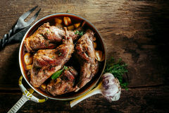 Roasted Rabbit Haunch in Pan on Rustic Wood Table Royalty Free Stock Images