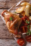 Roasted rabbit leg with apples and tomatoes top view vertical Royalty Free Stock Image