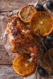 Roasted rabbit leg with oranges and olives on a paper top view Royalty Free Stock Photos
