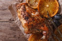 Roasted rabbit leg with oranges, olives and rosemary top view Stock Photography
