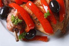 Roasted rabbit leg with peppers macro. horizontal top view Royalty Free Stock Images