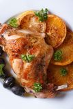 Roasted rabbit leg on a plate close-up. Vertical top view Stock Images