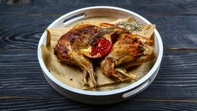 Roasted rabbit with pomegranate and rosemary on a paper on the old table. horizontal view from above, rustic style stock photography
