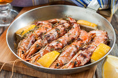 Roasted red Argentinean shrimp in a pan with lemon and herbs Stock Photo