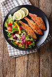 Roasted red mullet with fresh vegetables and lemon close-up. Ver Stock Images