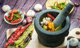 Roasted Red orange and green chili Peppers in pestle. With mortar and Grilled red  green and orange chili Peppers on background ingredients for making a curry Stock Images