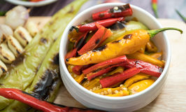 Roasted Red orange and green chili Peppers. In pestle with mortar and Grilled red  green and orange chili Peppers on background ingredients for making a curry Stock Photo
