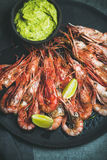 Roasted red shrimps with guacamole avocado sauce and lemon slices Stock Photography