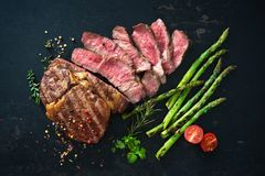 Roasted rib eye steak with green asparagus. On old sheet royalty free stock photo