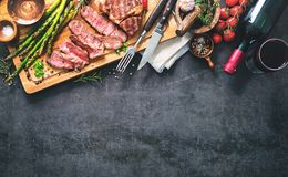 Roasted rib eye steak with green asparagus and wine. On dark background stock images