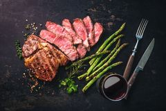 Roasted rib eye steak with green asparagus and wine. On dark background royalty free stock images
