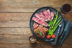 Roasted rib eye steak with green asparagus and wine. On wooden table stock image