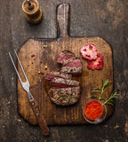 Roasted  ribeye steak sliced ​​on a cutting board with a fork, red sauce, peppers and tomatoes on rustic wooden background, Royalty Free Stock Image