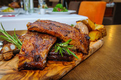 Roasted ribs close-up. Roasted ribs on a wooden board with herbs and roasted potatoes and sauerkraut stock photography
