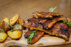 Roasted ribs with herbs. Roasted ribs on a wooden board with herbs and roasted potatoes royalty free stock photos