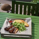 Roasted ribs, served on a tray , in sesame and cabbage salad vegetarian. street food Fron view. Stock Image