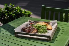 Roasted ribs, served on a tray , in sesame and cabbage salad vegetarian. street food Fron view. Stock Photo