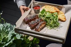 Roasted ribs, served on a tray , in sesame and cabbage salad vegetarian. street food Fron view. Close-up royalty free stock photo