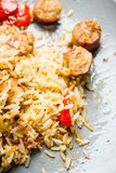 Roasted rice with grilled sausages and bell pepper on the wooden table royalty free stock photo