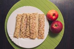 Roasted rodó las crepes en una placa redonda blanca y dos manzanas cerca Visión superior Endecha plana Fotografía de archivo
