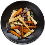 Roasted Root Vegetables Top View. Roasted root vegetables in black platter, isolated.  Top view Royalty Free Stock Image