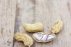 Roasted or row peanuts scattered on rustic, dark wood table back. Ground. healthy food background with copy space for use Stock Photo