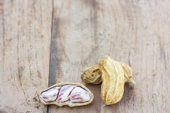 Roasted or row peanuts scattered on rustic, dark wood table back. Ground. healthy food background with copy space for use Royalty Free Stock Images