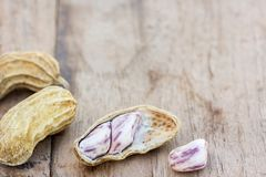 Roasted or row peanuts scattered on rustic, dark wood table back. Ground. healthy food background with copy space for use Royalty Free Stock Image