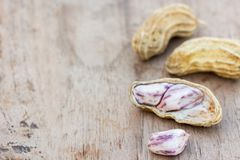 Roasted or row peanuts scattered on rustic, dark wood table back. Ground. healthy food background with copy space for use Stock Photography