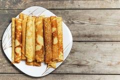 Roasted rullade pannkakor på en fyrkantig platta Arkivfoto