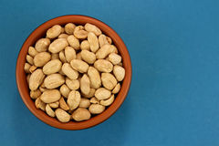 Roasted saló los cacahuetes en cuenco en el fondo azul, visión superior Imagen de archivo