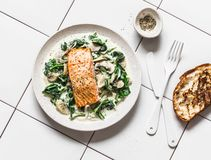 Roasted salmon with creamy spinach mushrooms sauce on a light background, top view. Salmon florentine.  stock photography
