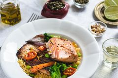 Roasted Salmon Fillet with Vegetables on Rustic White Plate. Healthy Food Concept stock image