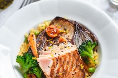 Roasted Salmon Fillet with Vegetables on Rustic White Plate. Healthy Food Concept royalty free stock photo