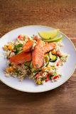Roasted salmon fish with tomato couscous, zucchini and lime on white plate. Vertical stock photo